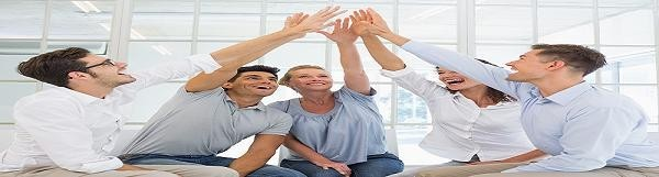 Group therapy in session sitting in a circle high fiving in a br